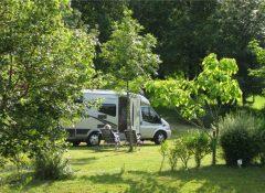 Un emplacement de camping arboré dans le camping Le Repaire à Thiviers